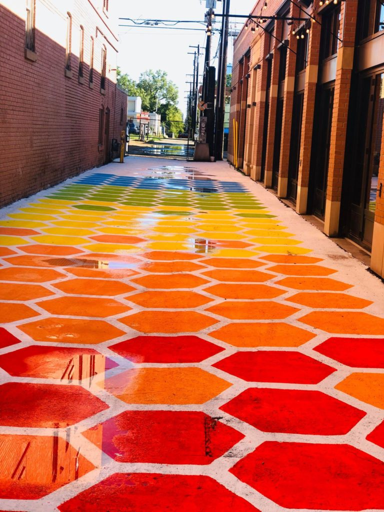 Hexagons in colours of the rainbow stretch down an alley