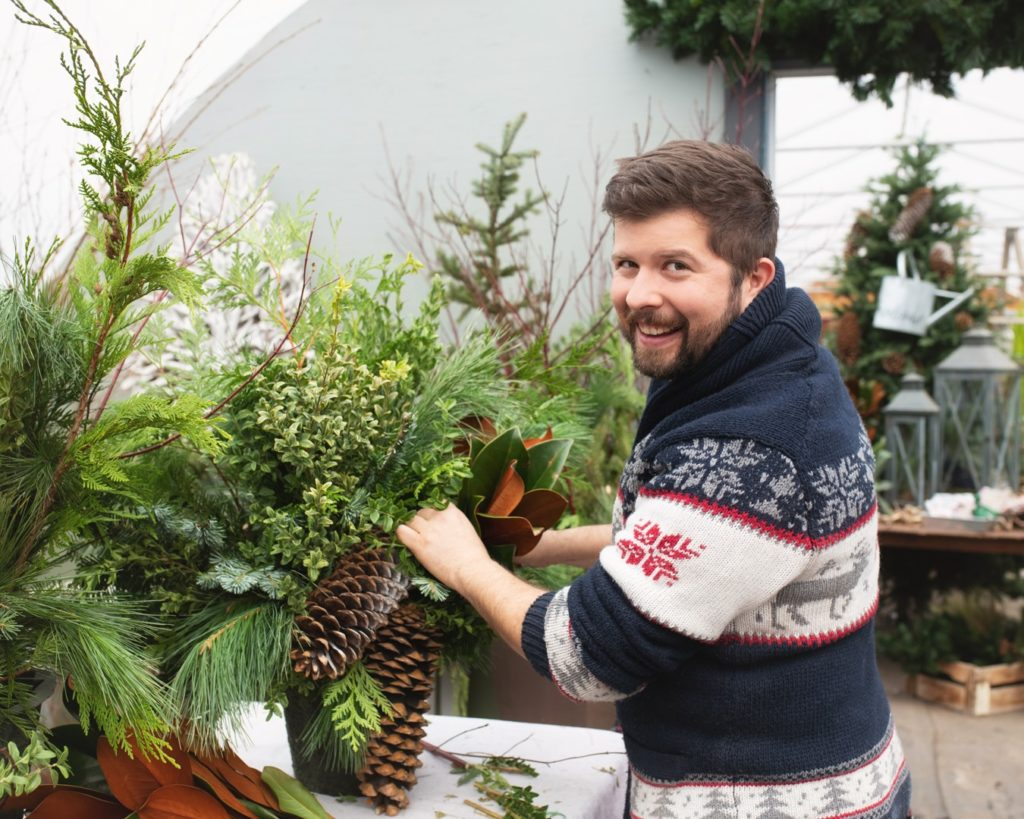 Wearing a reindeer sweater, Cory works on a holiday decoration