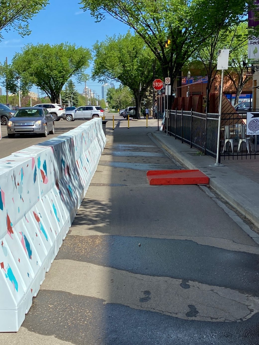 Brightly painted barriers separate vehicle lanes from pedestrian space on 102 Street