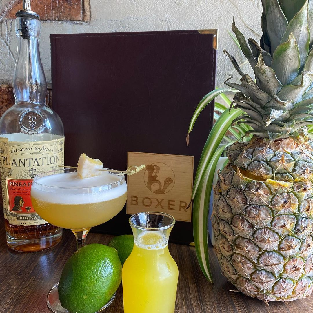 A pineapple sits beside bar ingredients and a yellow cocktail