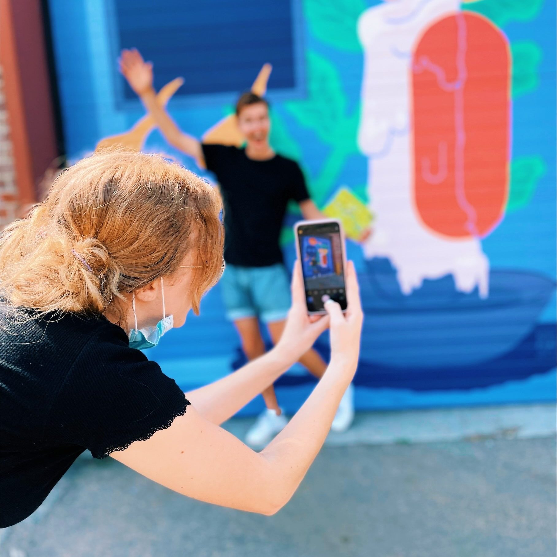 A young woman leans over to take a photo of a young man excitedly throwing his arms out in front of a brightly coloured mural.