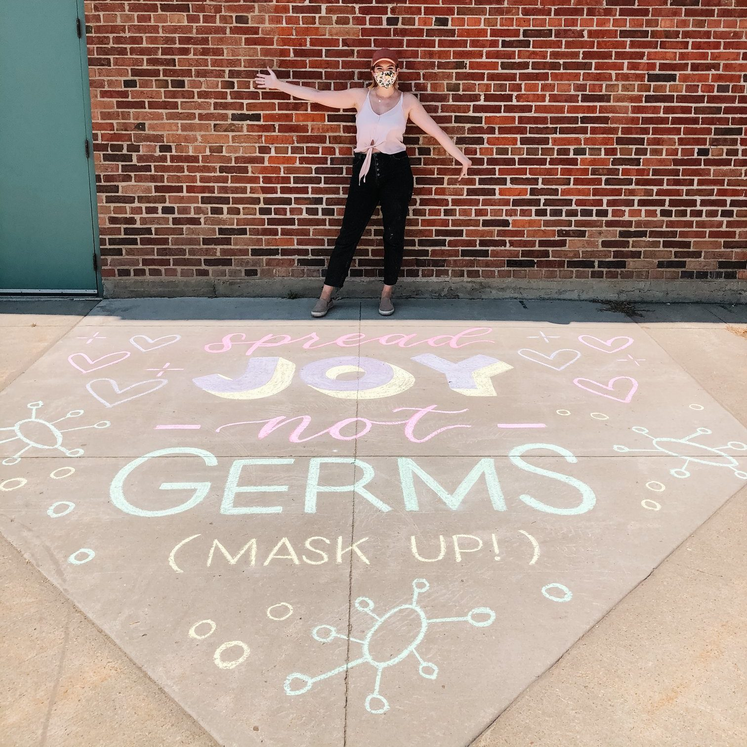 An artist in a mask poses in front of a chalk message reading Spread Joy Not Germs, Mask Up