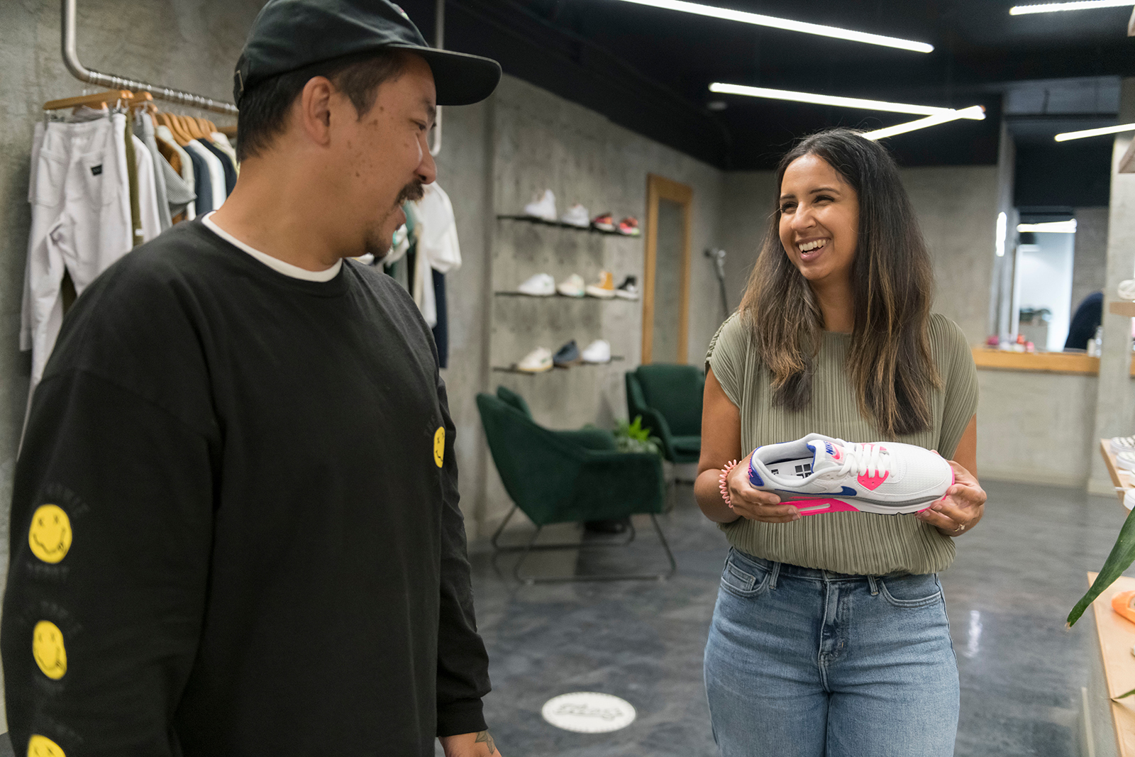 A woman shopping for shoes smiles with a store owner while they talk about the running shoe she's checking out