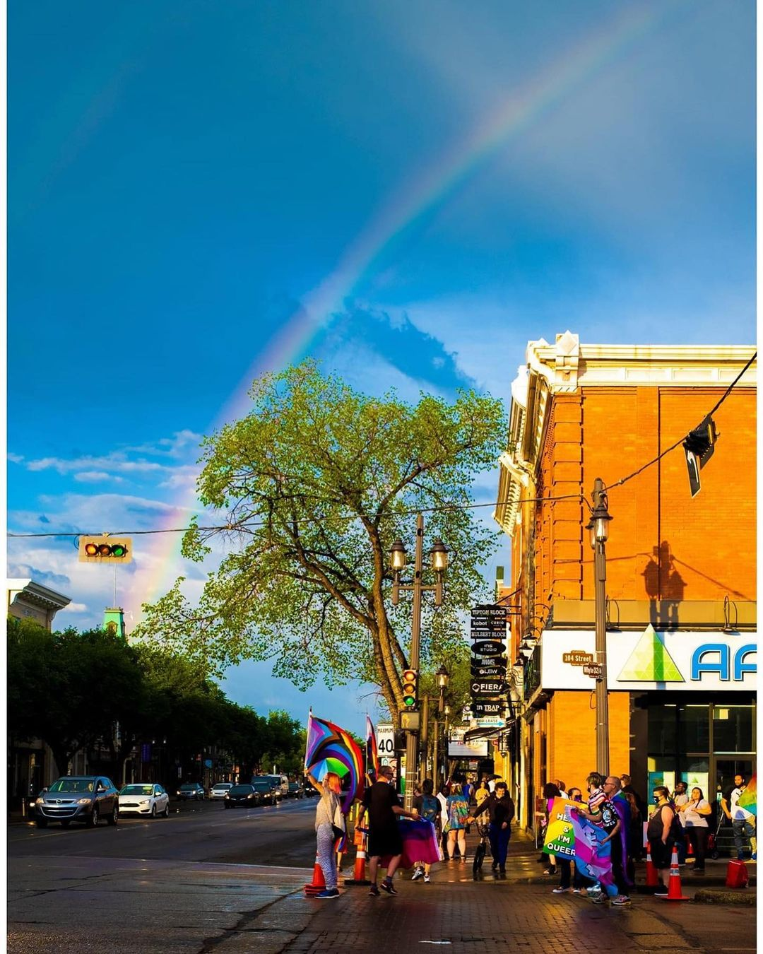 Protestors wave Pride Progress rainbow flags on Whyte Avenue with a rainbow above in the sky